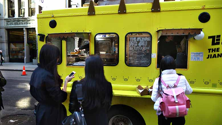 Clientes esperan su Jianbing en el carrito de Flying Pig, en las calles de Nueva York.