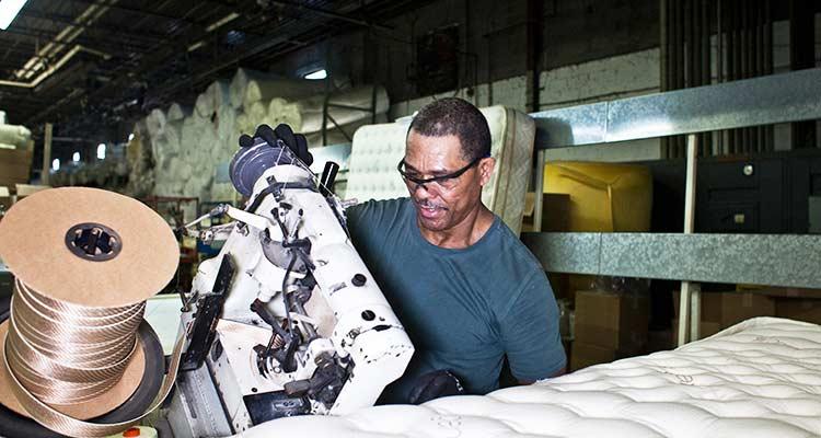 Un trabajador utiliza una máquina de coser en una fábrica de colchones Saatva. / Foto: The New York Times.